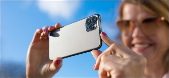 A woman taking a picture with an iPhone.