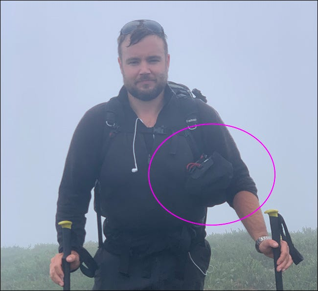 A man walking in the rain carrying a tripod and a Peak Design Camera Shell bag.