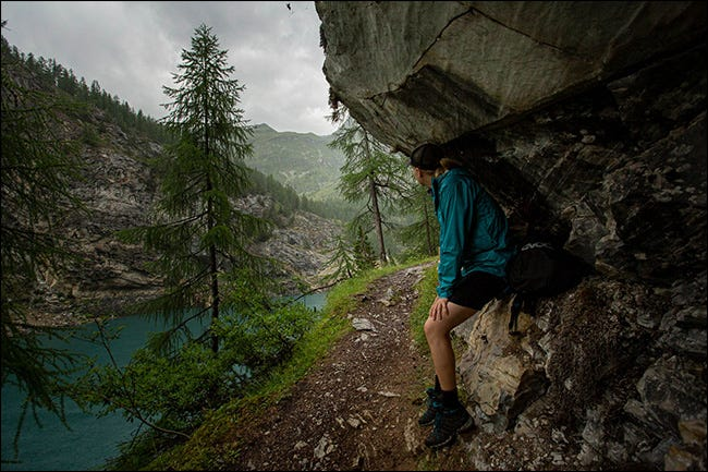 A woman sheltering from the rain under a cliff in the mountains.