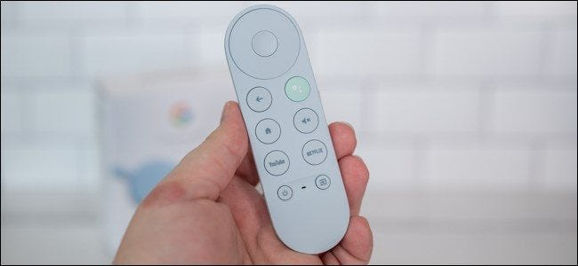 Someone holding a Chromecast with a Google TV remote in hand.