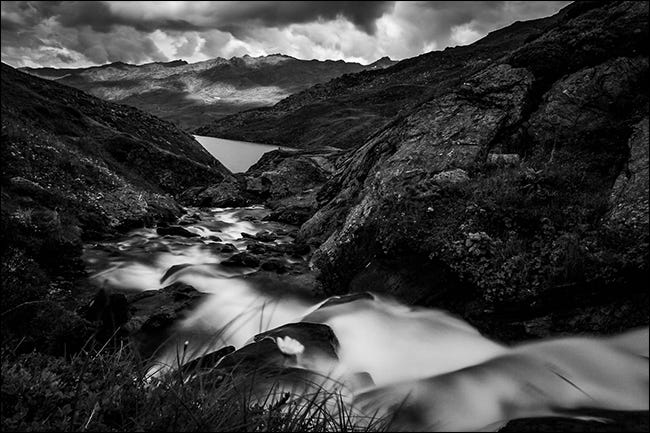A black and white photo of a stream in the mountains after it rained.