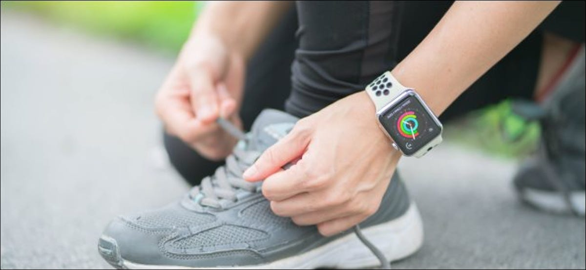 A woman tying her shoelaces while wearing an Apple Watch.