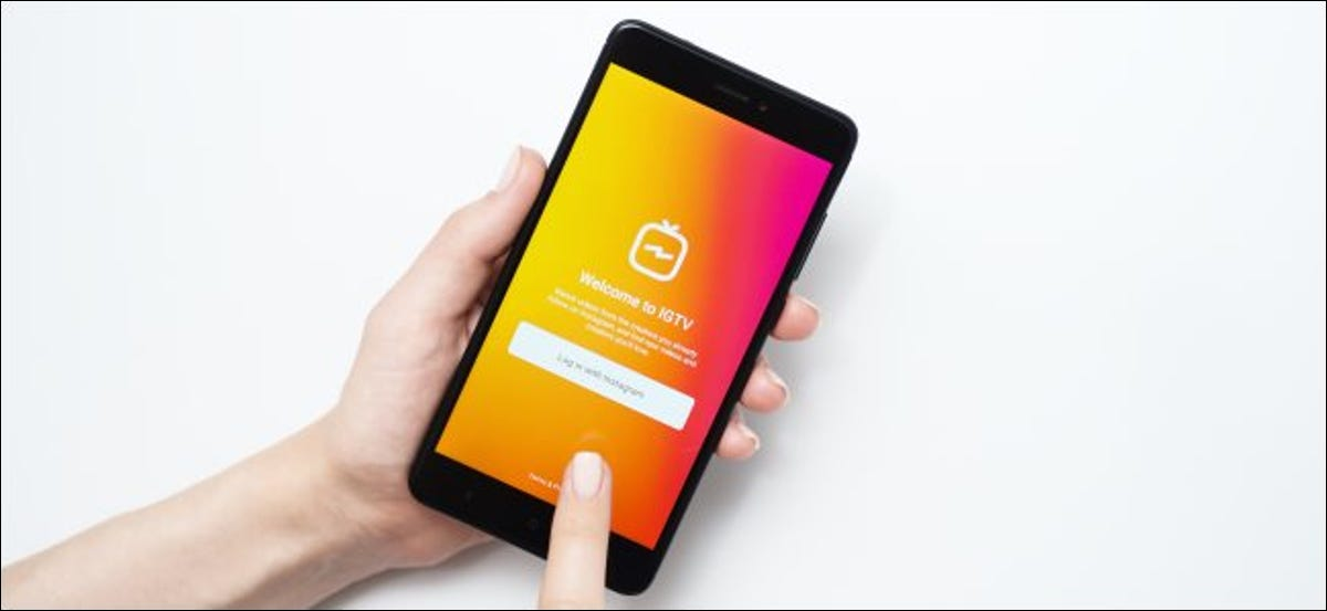 A finger tapping the IGTV app login screen on a phone.