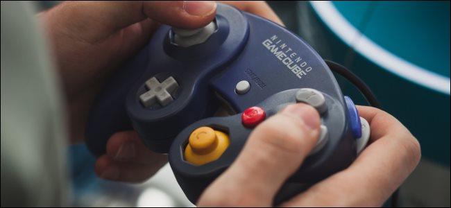 Hands holding a Nintendo GameCube controller.