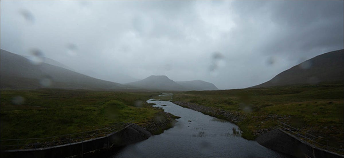A mountain and stream on a cloudy, wet day.