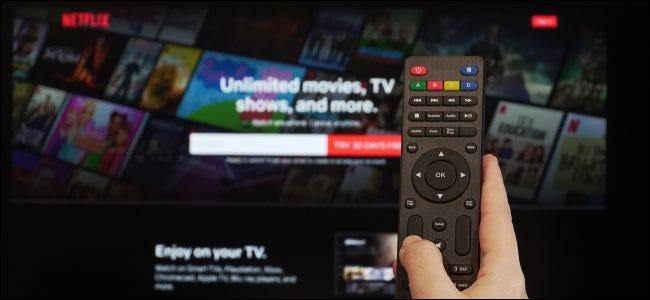 A hand holding a remote in front of the Netflix sign-up screen on a TV.