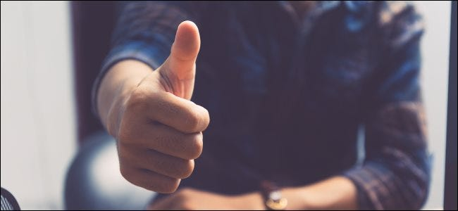 A person giving a thumbs up at a desk.