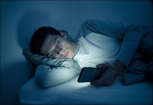 A man texting on his smartphone in bed at night.