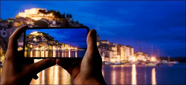 A smartphone taking a photo of a city and sea at night.