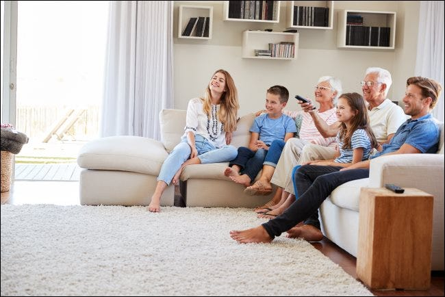 A family sitting on a couch watching a TV.