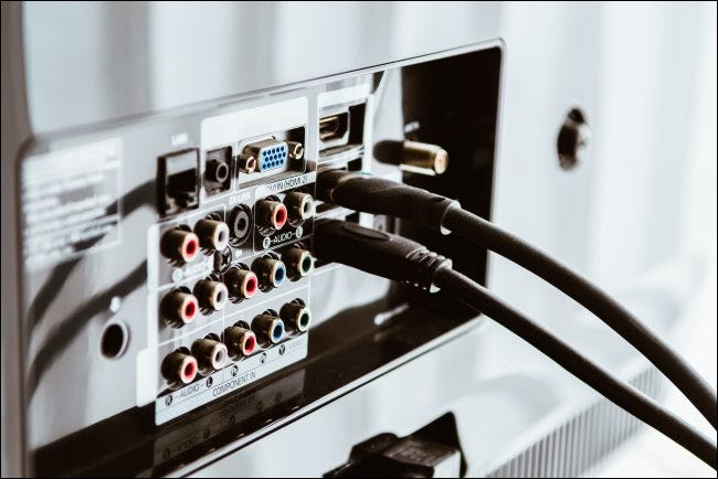 HDMI cables connected to the back of a television set.