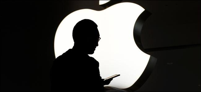 A silhueta de uma pessoa usando um iPhone na frente de um logotipo da Apple.