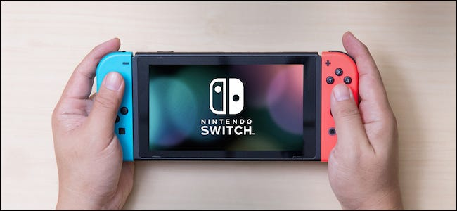 Nintendo Switch console in hand