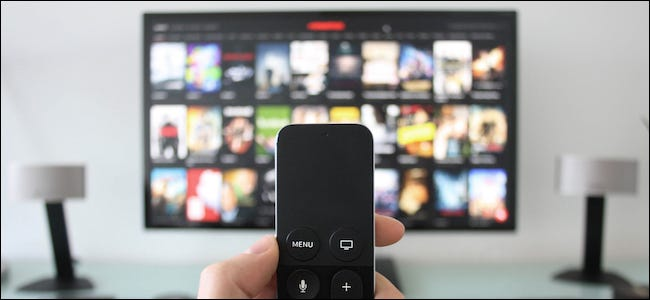 Person holding a remote while streaming movies