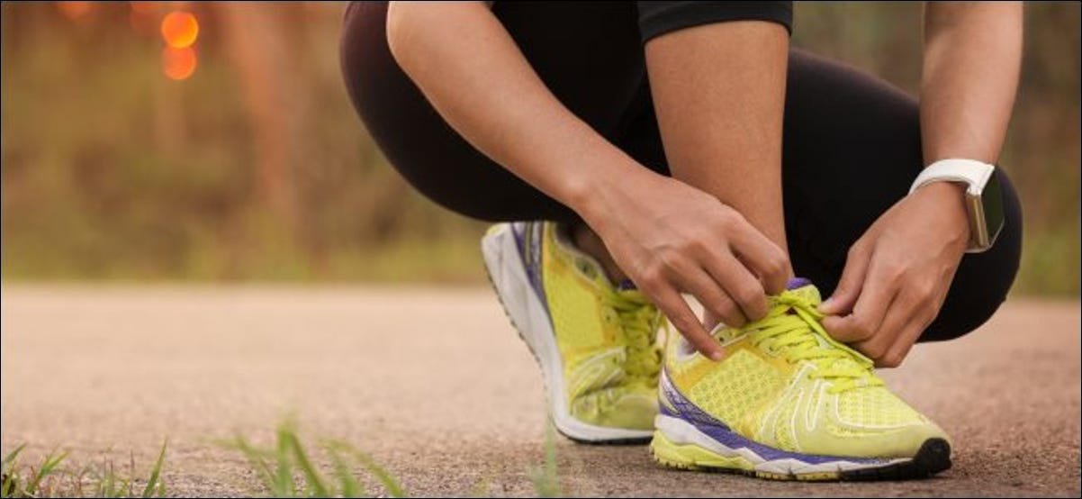 A person tying their shoes before a run while wearing a smart watch.