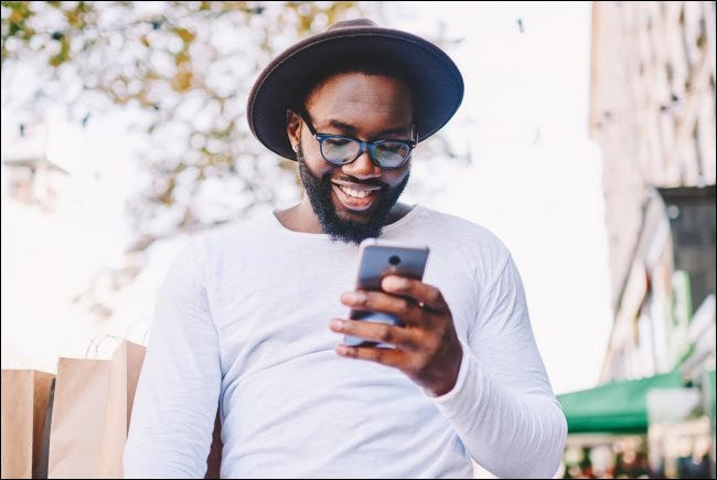 A person smiling while looking at a smartphone.