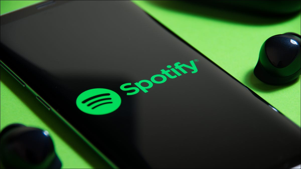 Spotify logo on a smartphone next to truly wireless earbuds