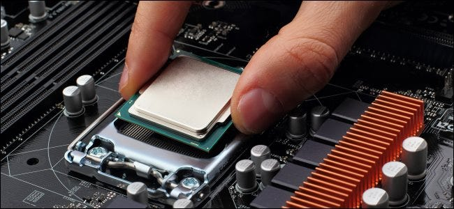 A hand plugging a CPU into a socket on a motherboard.