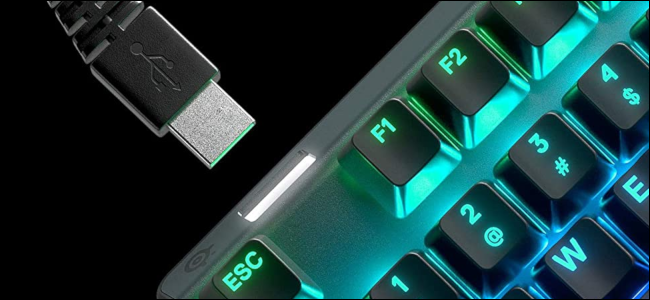 An RGB-illuminated keyboard with a USB cable being inserted into a USB passthrough port.