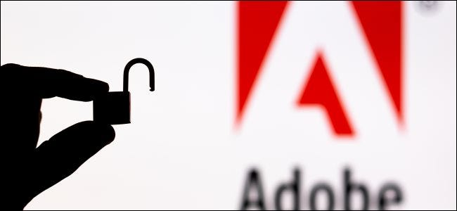 A silhouette of a hand holding an unlocked padlock in front of an Adobe logo.
