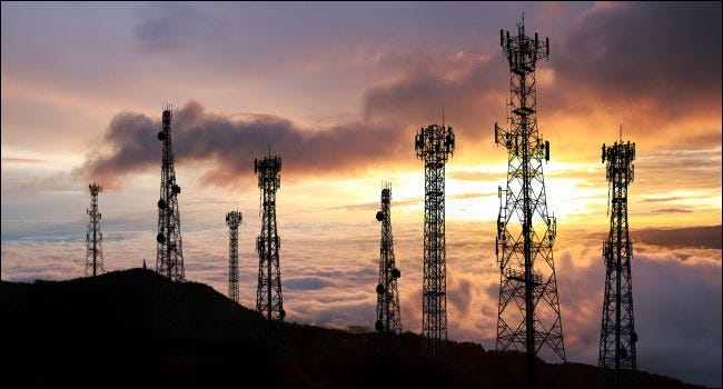 Cellular towers in front of a sunset background.