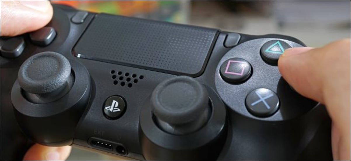 Hands holding a Sony DualShock 4 controller.