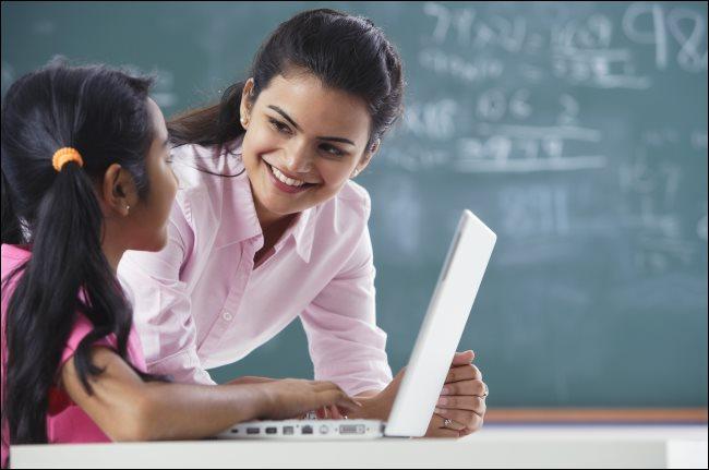 Egy tanár, aki egy fiatal diákot tanít egy laptop előtt.