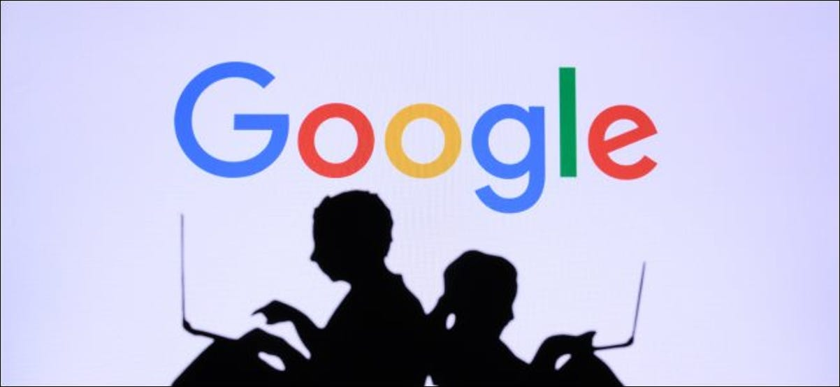 Silhouettes of two people using laptops in front of a Google logo