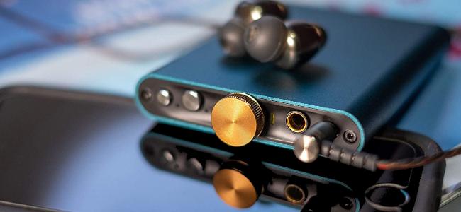 An aqua marine portable DAC resting on top of a smartphone.