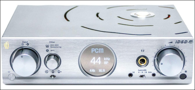 An external DAC with silver chassis and circular LCD display.