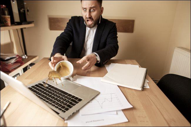 Egy ember ömlött a kávé egy laptop.