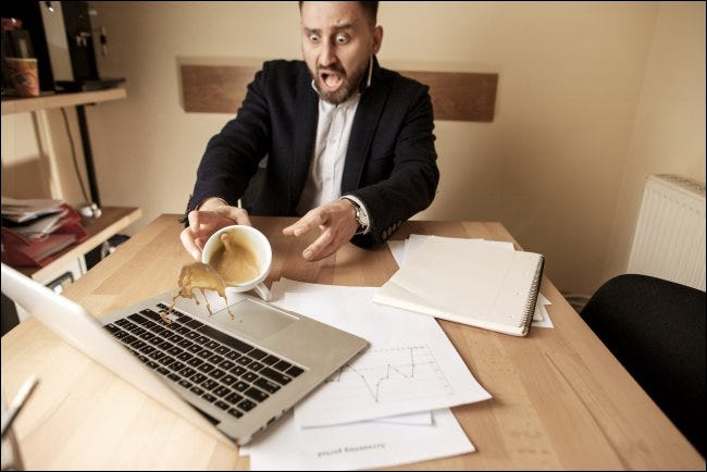 A man spilling coffee on a laptop.