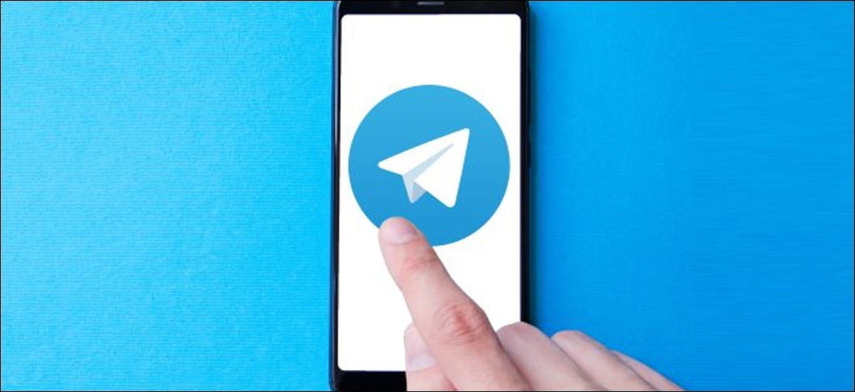 A finger tapping a large Telegram app icon on a smartphone.