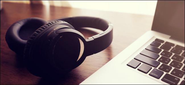 Bluetooth headphones laying next to a Mac