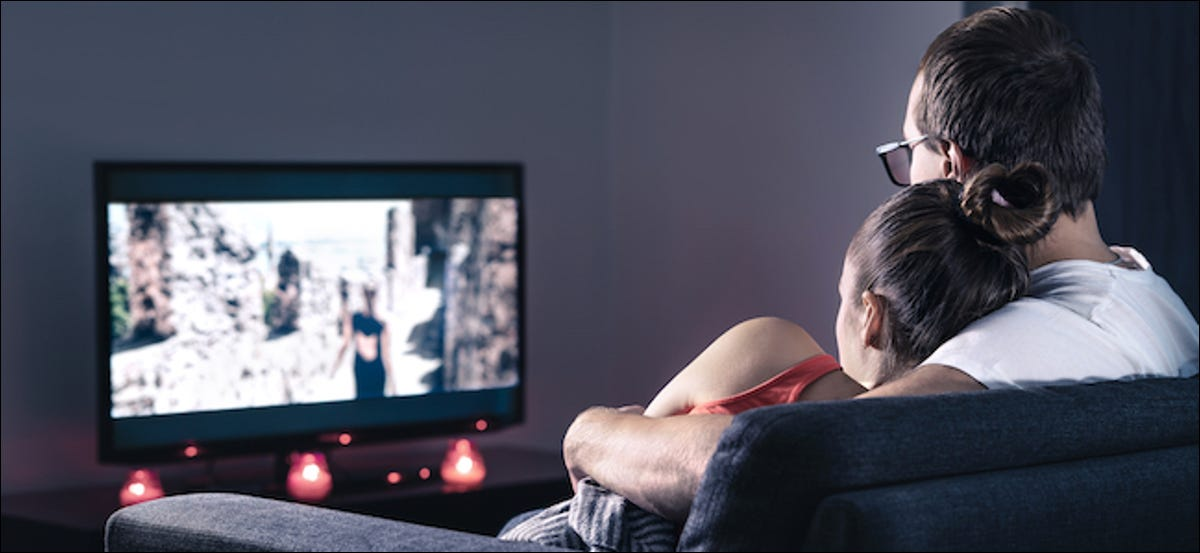 Couple on a couch watching rom-com movies on Valentine's Day