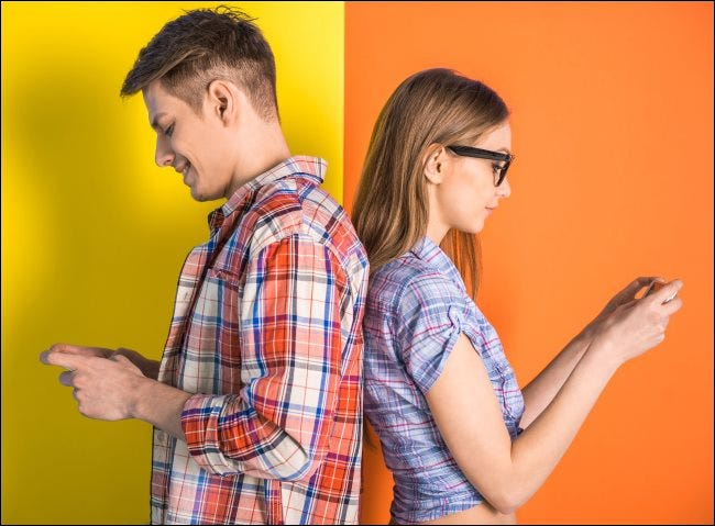 A couple standing back-to-back while texting.