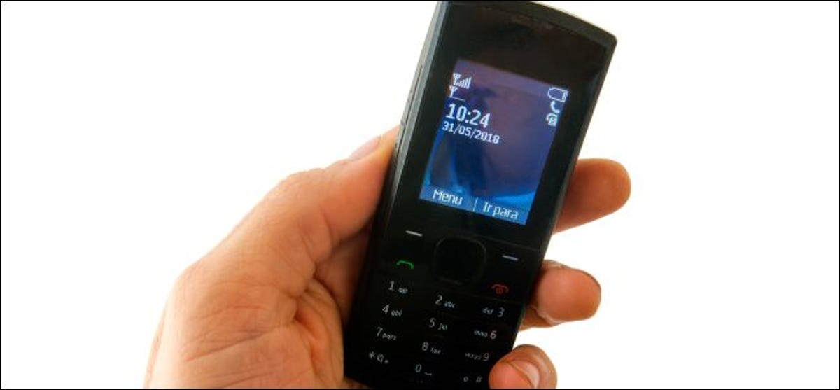 A hand holding an old feature phone.