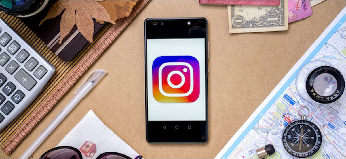 Instagram logo on a smartphone surrounded by travel gear