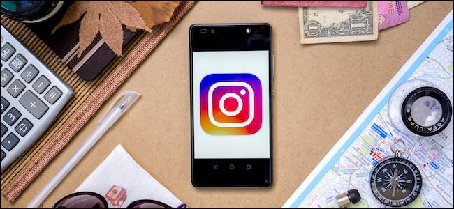 Logo di Instagram su uno smartphone circondato da attrezzatura da viaggio