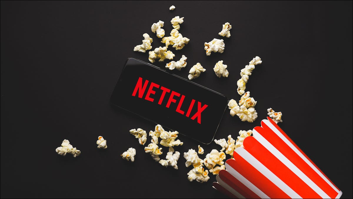 Netflix logo on a smartphone next to popcorn