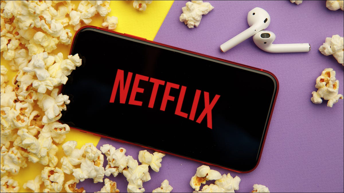 Netflix logo on an iPhone and next to AirPods and popcorn