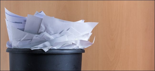 A trash can overflowing with papers.