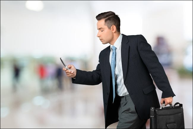 A hurried businessman texting.
