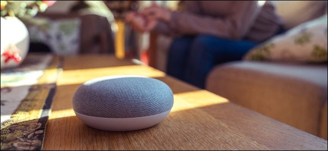 Smart speaker sitting on a table with a person in the background.
