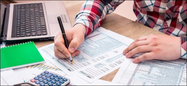 Человек заполняет 1040 налоговых бланков на бумаге возле ноутбука.