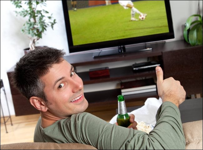 A man giving a thumbs up in front of a TV.