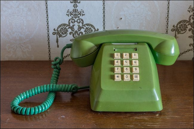 A vintage touch-tone telephone on a wooden table.