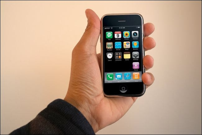 A hand holding a first-generation iPhone.