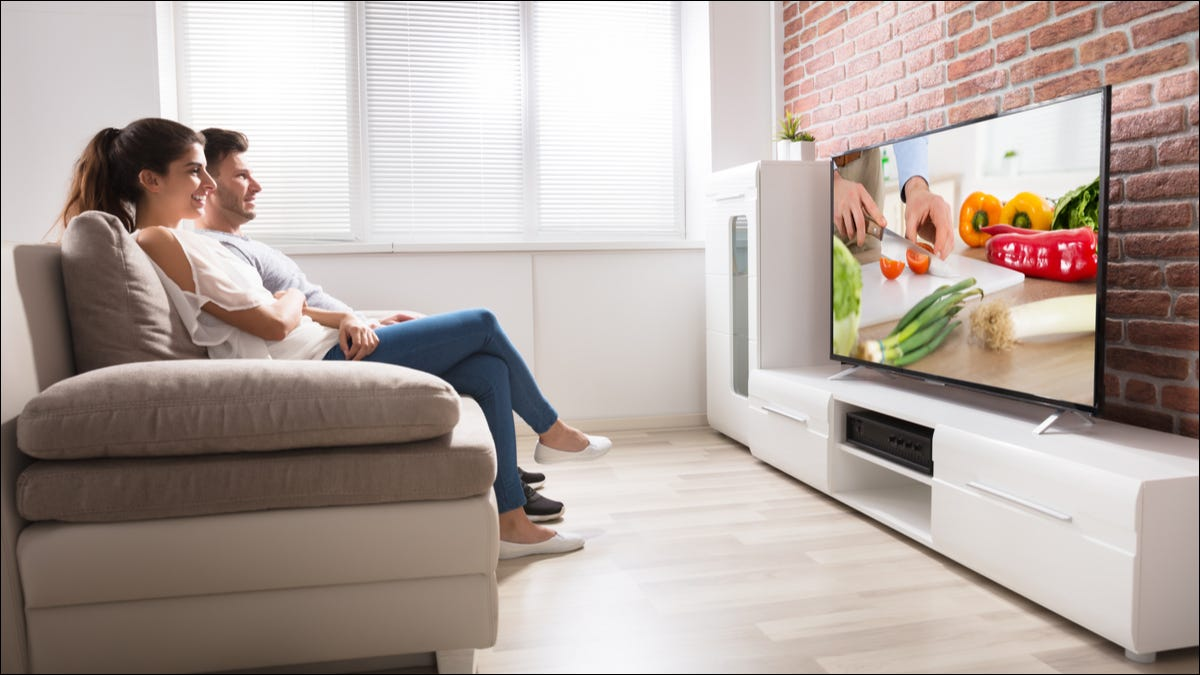 A couple watching a food TV show on television
