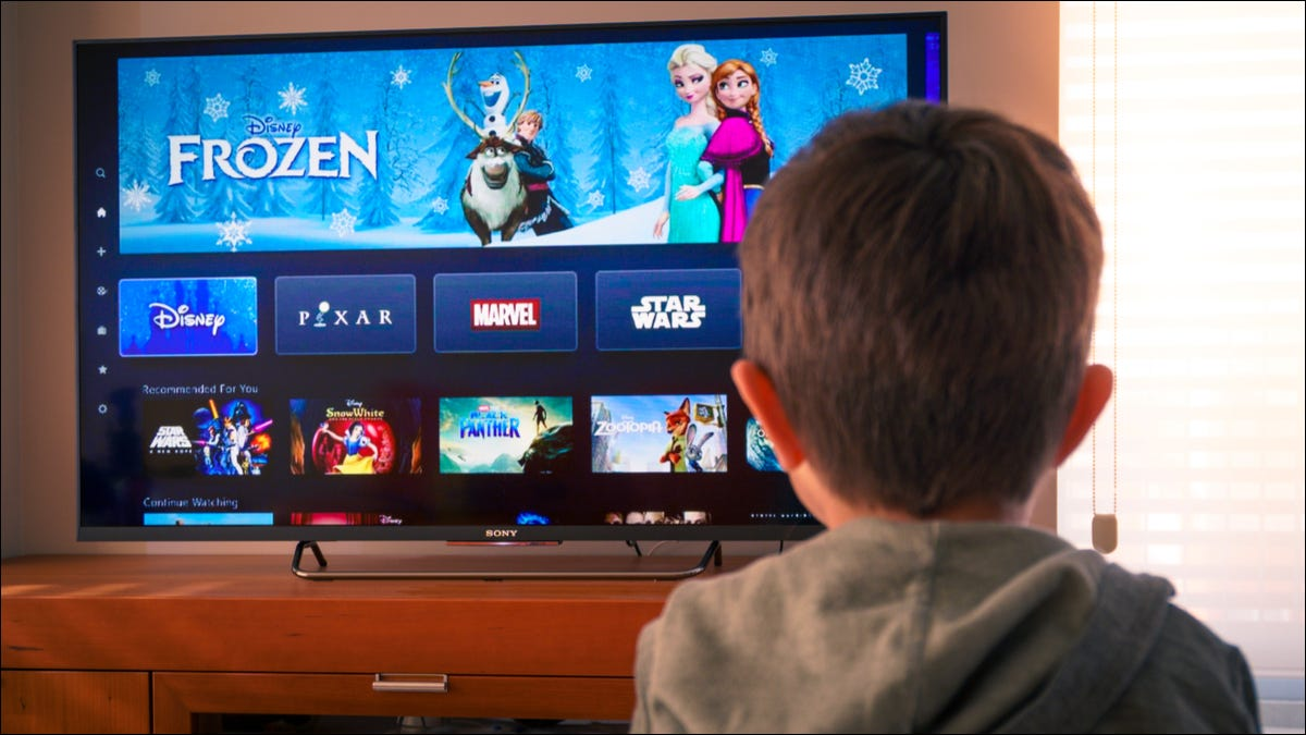 A kid watching Disney+ on a TV
